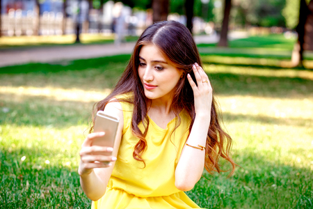yellow dress: young girl with phone in park at summer in yellow dress at sunny day