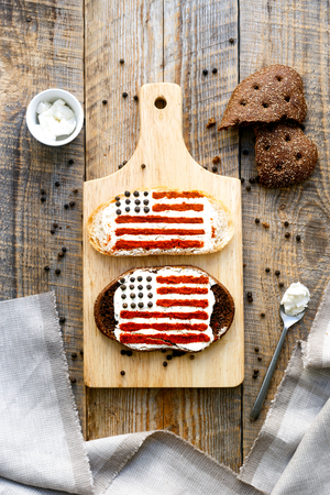two on top: Two sandwiches with image of american flag on wooden table, top view. Stock Photo