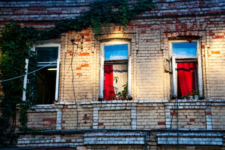 open windows: three open windows on a brick building in the evening