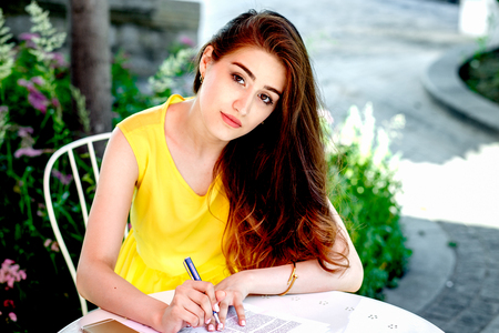 yellow dress: young woman taking notes in cafe at summer in yellow dress at sunny day