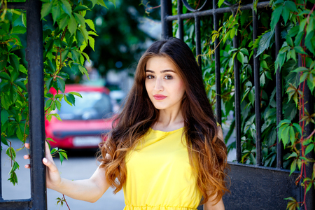 summer dress: young woman on city streets in summer in yellow dress.