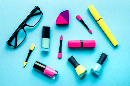 applicator: make up set on blue background with glasses top view.