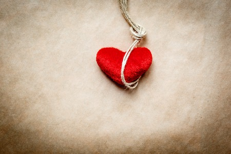 ahorcado: concepto del ahorcado nudo con el corazón rojo de peluche en el fondo de papel kraft