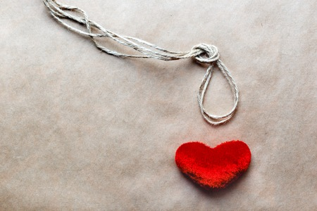 ahorcado: concepto del ahorcado nudo con el coraz�n rojo de peluche en el fondo de papel kraft