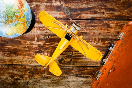 plane table: concept - time to travel plane, suitcase, globe on wooden table