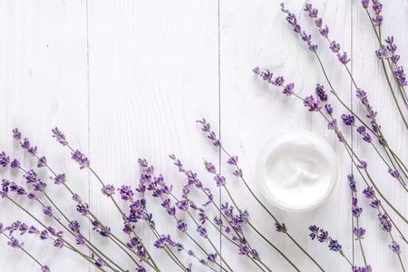 Crème visage lavande sur fond blanc en bois vue de dessus