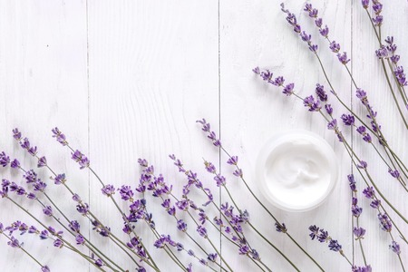 Lavender face cream on white wooden background top view