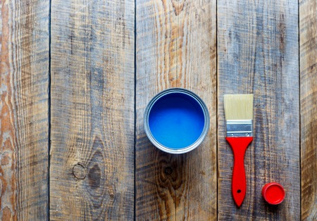 redecorating: painting at home with open can of blue paint and red brush on wooden background top view Stock Photo