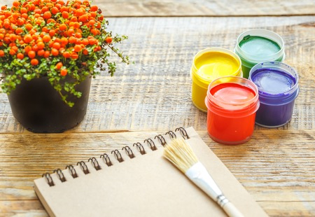 visual therapy: hobby painting - workplace with gouache jars, open blank notebook on wooden table