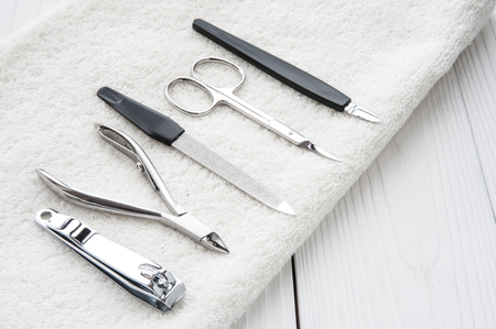manicure tools set nail care with fluffy towel top view on wooden background Imagens