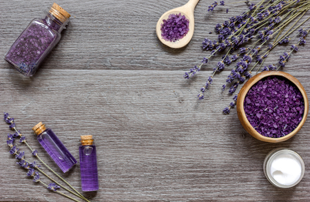 limpieza: cosmetic creams with lavender flowers on black wooden table top view Foto de archivo