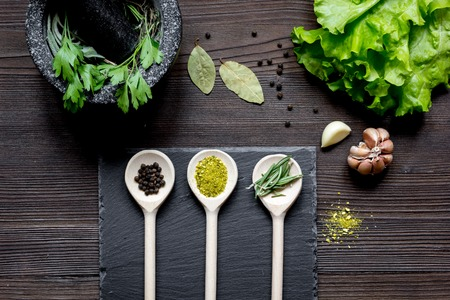 pounder: spices for cooking and fresh salad with pounder on wooden table top view