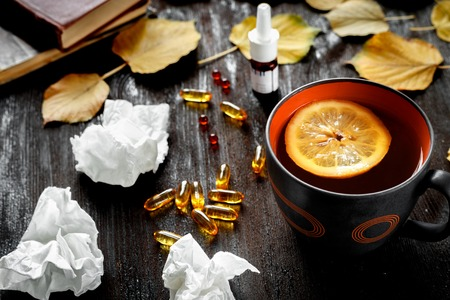 medecine: concept cold - treatment with hot tea and medecine on wooden background Stock Photo