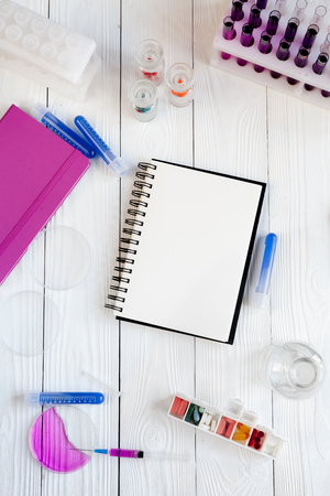 commercial medicine: medical student working place with blank open notebook at wooden table top view