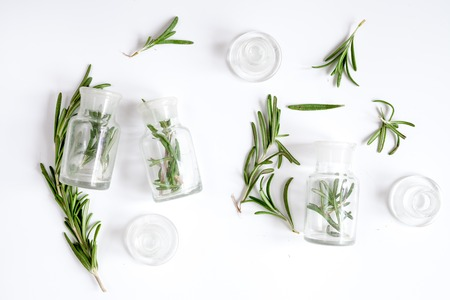 fresh rosemary with bottle on white background top view.
