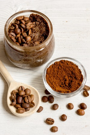 aroma facial: handmade coffee -cocoa scrub in glass jar on wooden background close up