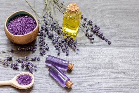 Essential oil and lavender salt with flowers top view wooden background