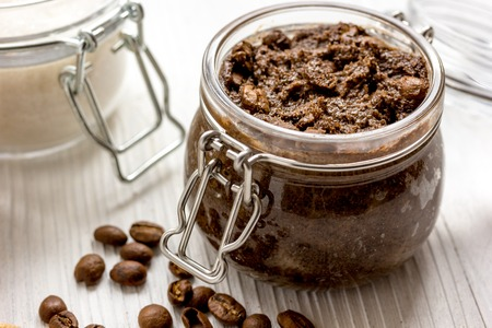 homemade coffe scrub in glass jar on wooden background. Imagens