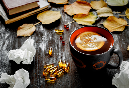 medecine: autumn cold - treatment with hot tea and medecine on wooden background