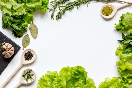frame spices for cooking and fresh herbs, salad on white table top view