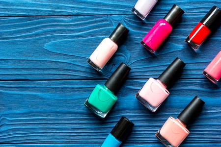 colored bottle: lot of bottles of nail polish on dark wooden background top view Stock Photo