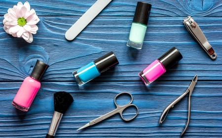 manicure set: flower, nail polish and manicure set on dark wooden background top view Stock Photo