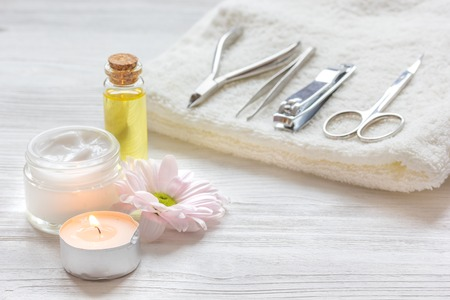 tea candle: spa nail care with tea candle, flower on wooden background