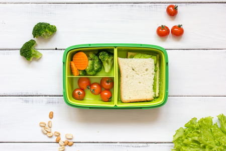 preparing lunch for child with vegetables and fruit to school top view on wooden background