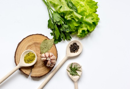 food additives: frame spices for cooking and fresh herbs, salad on white table top view