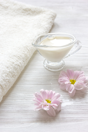 revitalizing: cream and spa on wooden background with flowers close up
