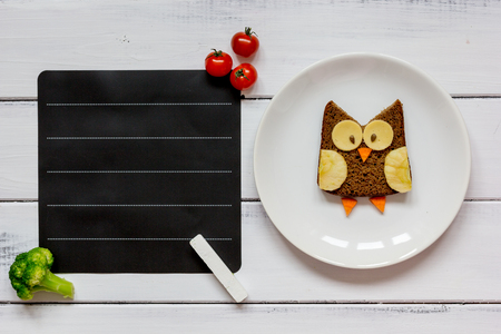 kids menu owl shaped sandwich with tomato place for text top view at wooden background