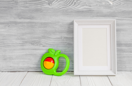 blank photo: baby rattle and photo frame on wooden background top view