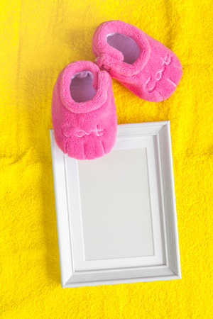 booties: pink booties and photo frame on yellow background top view Stock Photo