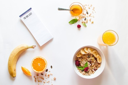 Breakfast with oatmeal and orange juice, to do list on white background top view Archivio Fotografico