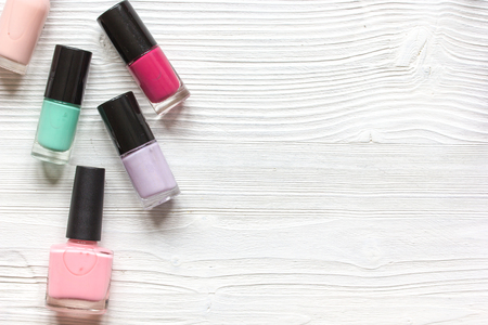 beautycare: group of nail polish on wooden background top view.