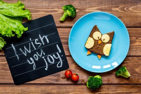 plato del buen comer: niños el desayuno en forma de sándwich de búho en azul vista de la placa superior en fondo de madera te deseo alegría Foto de archivo