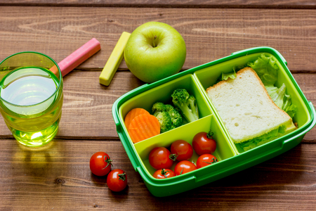 dinnertime: Healthy lunch box for student with juice on wooden background