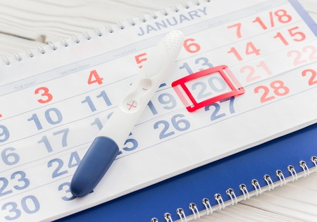 Positive pregnancy test with calendar close up top view Stock Photo