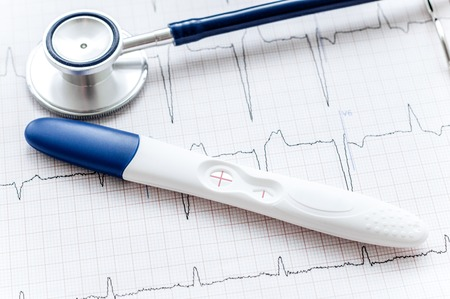 first miracle: Positive pregnancy test with stethoscope and diagram Stock Photo