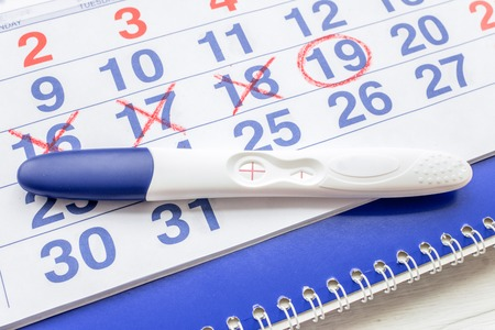 first miracle: Positive pregnancy test with calendar close up top view Stock Photo