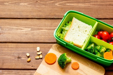 dinnertime: lunch box for kid with fresh vegetables on wooden background.