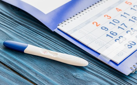 first miracle: Positive pregnancy test with calendar close up