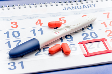 conceive: Positive pregnancy test with calendar close up top view Stock Photo