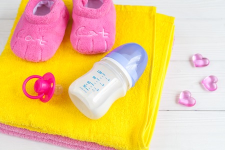 baby bottle with milk and towel on wooden background close up Stock Photo