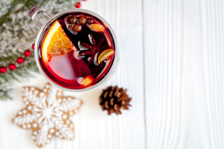Christmas mulled wine with spices in cup on wooden background top view