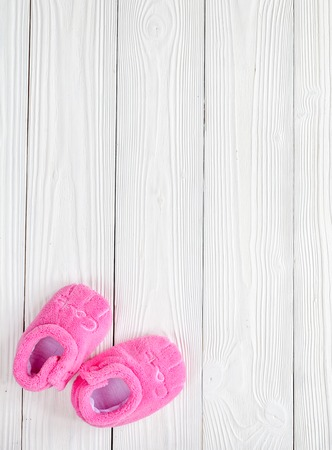 booties: pink booties on wooden background top view