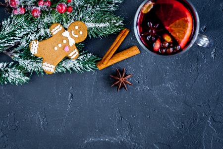 overturn: Christmas mulled wine with spices in cup on dark background top view