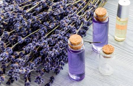 bath essence: Lavender and cosmetic oil on wooden background.