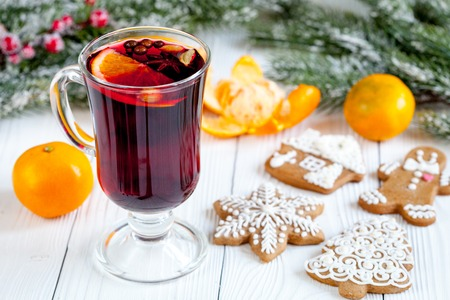 overturn: Christmas mulled wine with spices in cup on wooden background close up