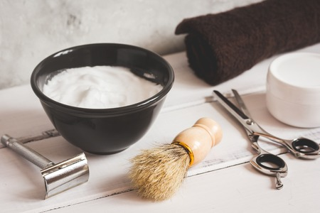 Mens hairdressing wooden desktop with tools for shaving close up Stock Photo